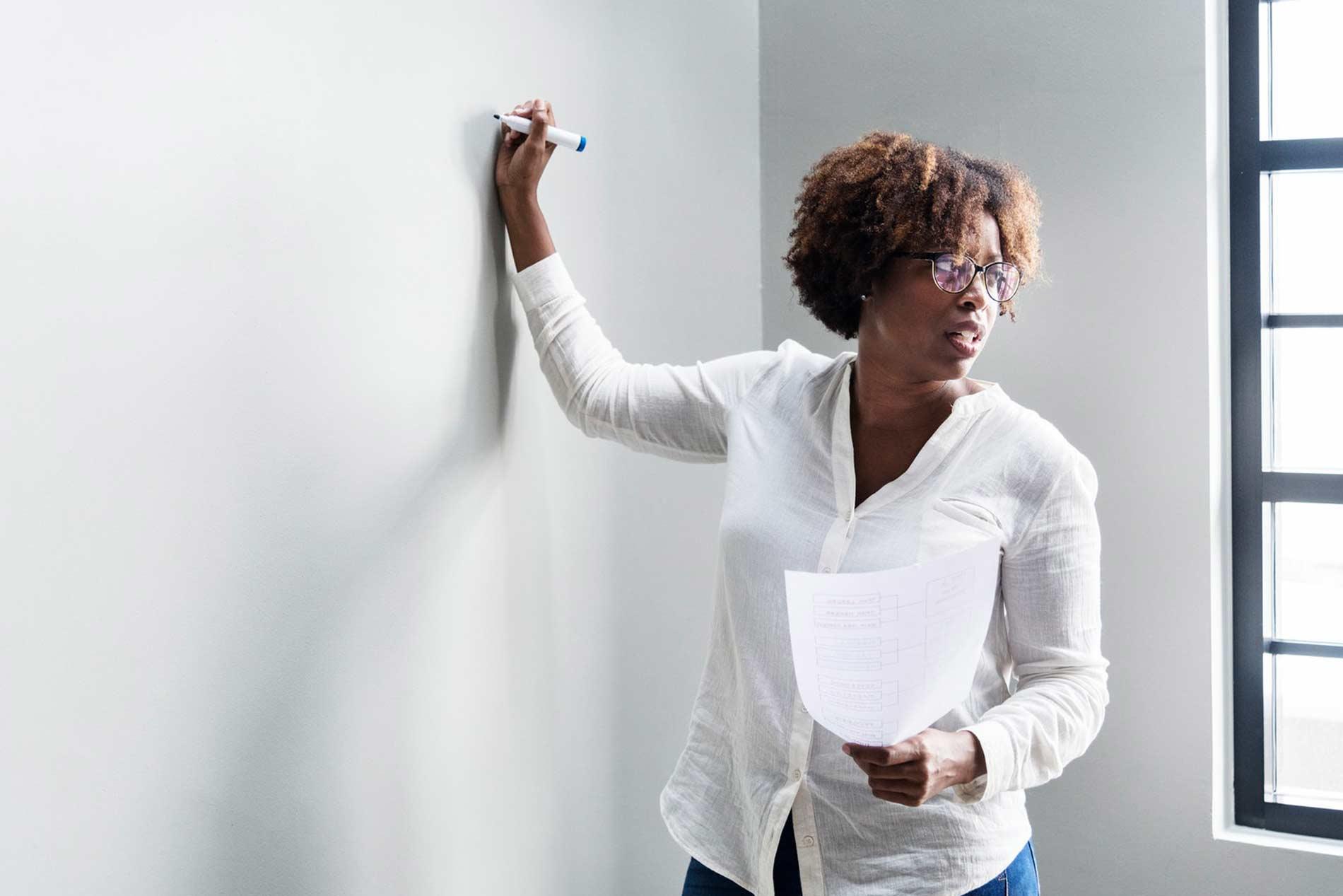 Mujer escribiendo en un tablero y con un hoja en la mano, mirando al público