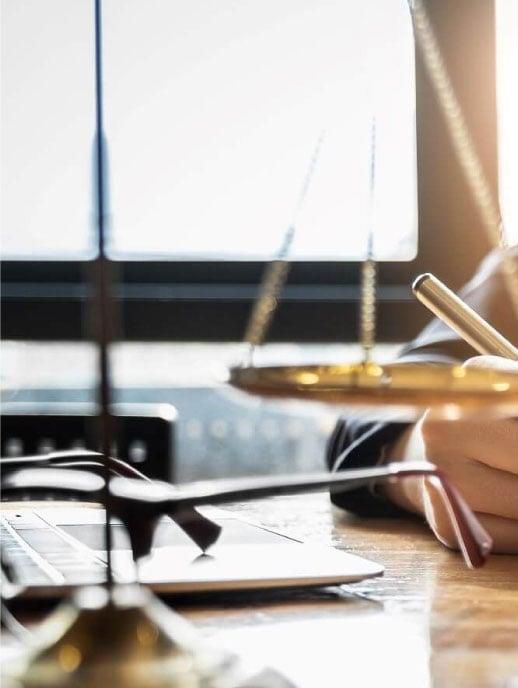 Acercamiento de una escala de equilibrio ubicada sobre un escritorio y delante de una persona escribiendo.
