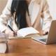 Mujer escribiendo en una cuaderno con un computador al frente