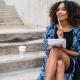 Mujer joven sentada en unas escaleras de cemento al aire libre, con un cuaderno y un lapicero, pensando para escribir.