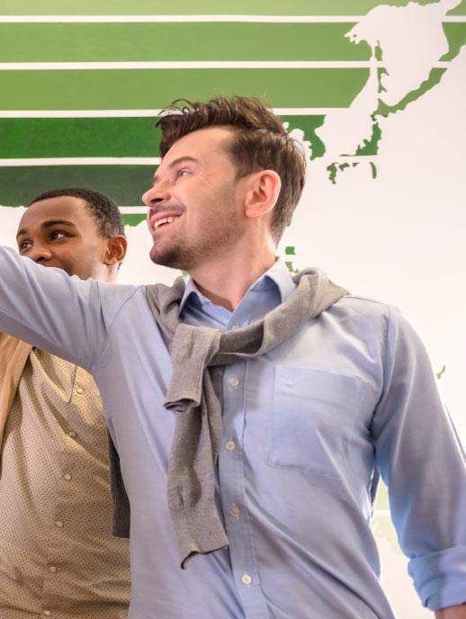Dos hombres profesionales chocando sus manos arriba, celebrando con un grupo.