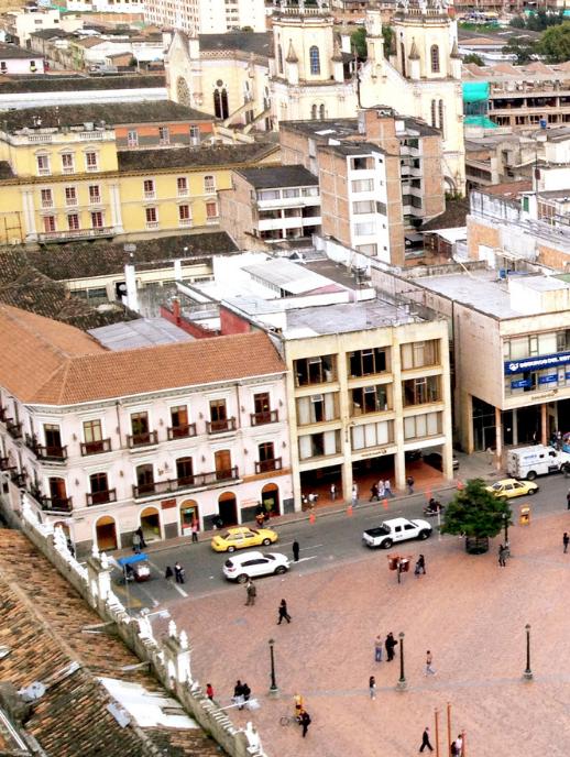 Vista aérea de una de las calles del Departamento de Nariño, Colombia, en donde se ven transeúntes, vehículos y edificios.