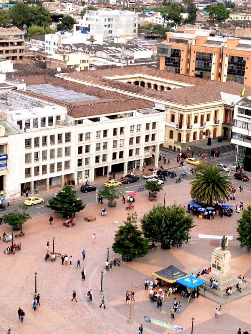 Fotografía aérea de un parque del Departamento de Nariño, Colombia, en donde se ven personas caminando, vehículos en la calle y edificios.