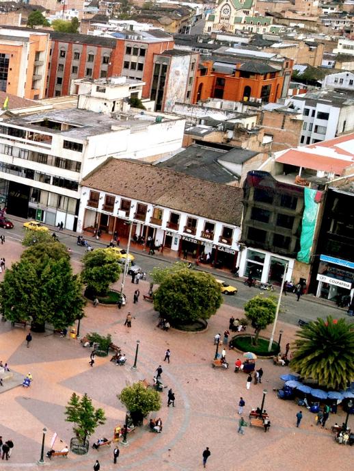 Vista aérea un parque del Departamento de Nariño, Colombia, en donde se ven transeúntes, árboles y edificios.