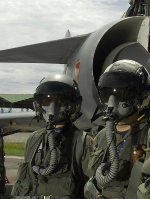 Dos pilotos de la fuerza aérea con máscaras de vuelo al frente de un avión de combate.